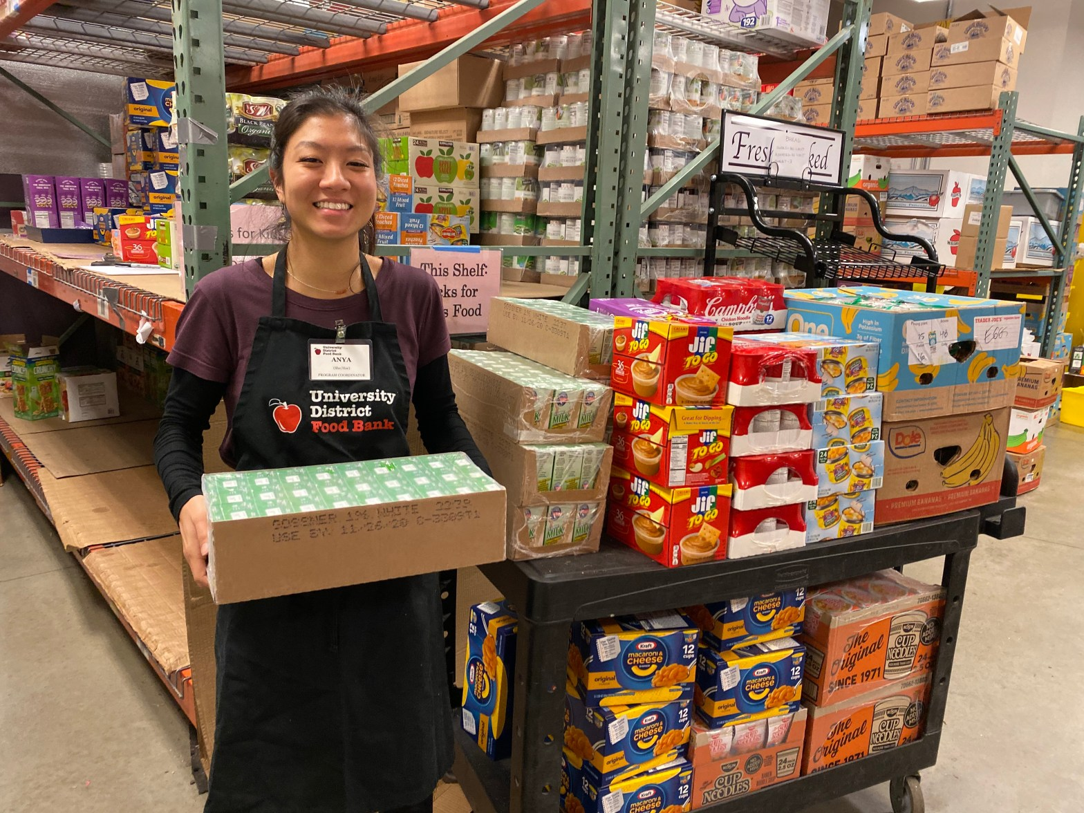 WSC member Anya serving with the University District Food Bank in Seattle, WA, posing with donated food in warehouse.