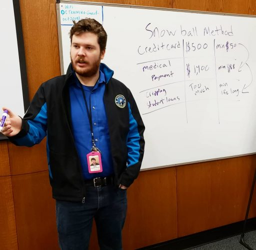 WSC member Grady, serving with Opportunity Council in Bellingham stands in front of a dry-erase board with financial terms on it.