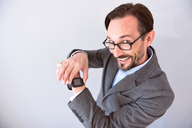 It is very useful. Confident mature man with smile on his face touching and showing a smart watch on his wrist isolated on the grey background