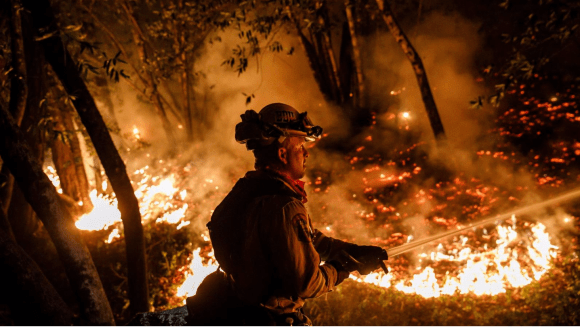 Cal Fire firefighter Mario Topete sprays water to help prevent flames from crossing Highway 29, north of Calistoga on Thursday. (Marcus Yam/Los Angeles Times)