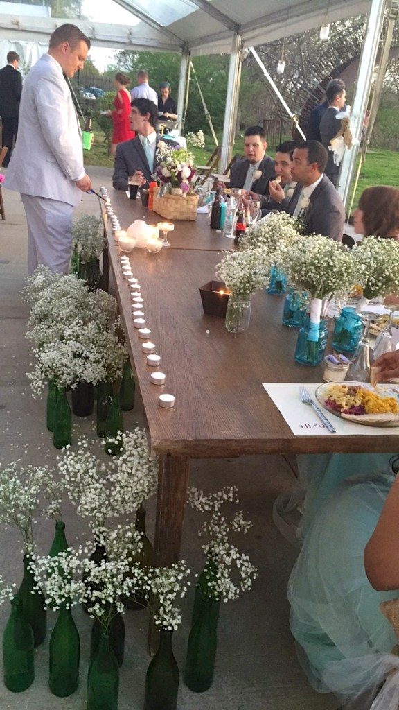 The head table was a rented farmhouse table, kept simple with bunches of white flowers and candles.