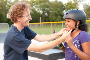 Man helping fit a girl with a helmet at a skate park