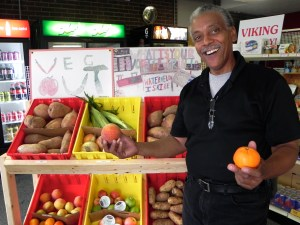 Joe Martin standing in front of bins of produce holding an orange and a peach