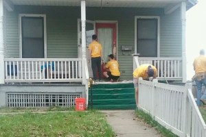 workers scraping and painting front porch of house