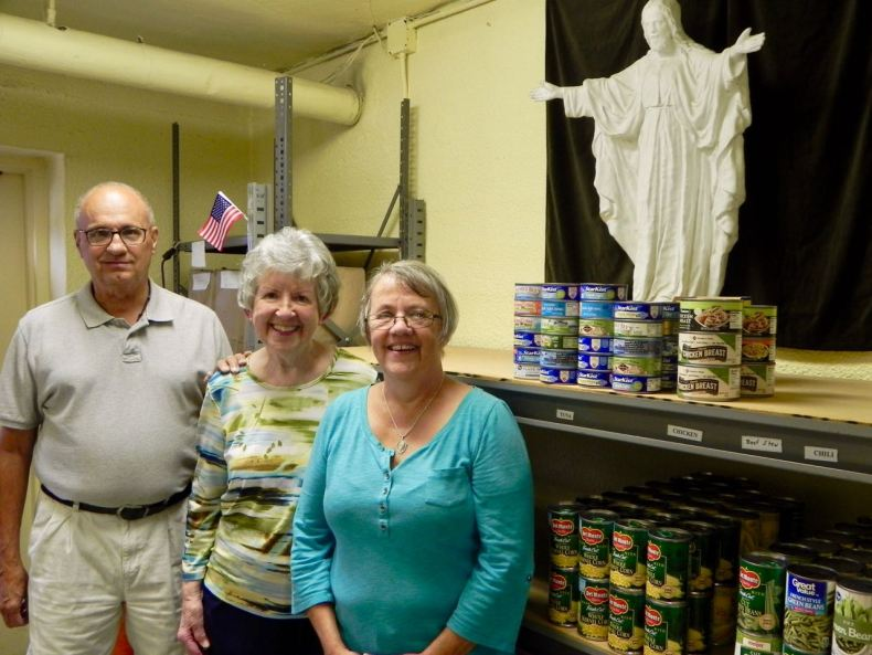 Three adult volunteers in front of food pantry shelf