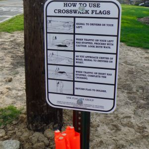 sign explaining to pedestrians how to use crosswalk flags to alert traffic to cross safely.