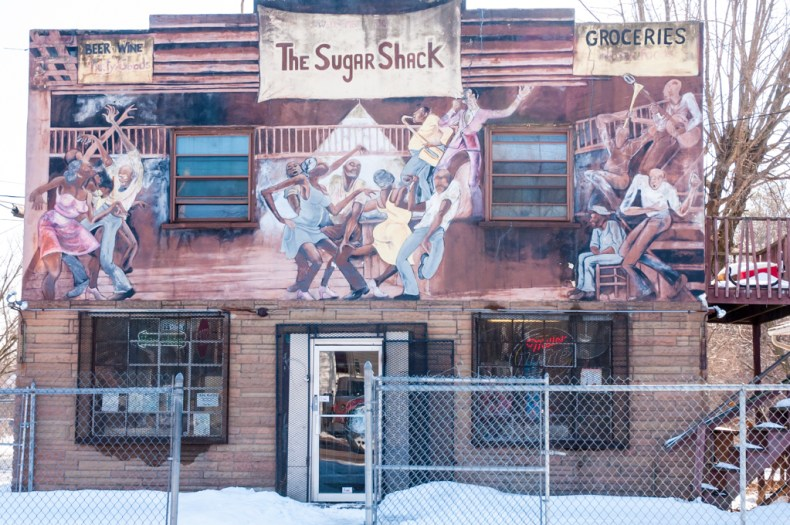two story building with sign reading The Sugar Shack, groceries, beer and wine, paintings of people dancing and playing music