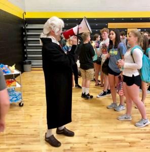 man dressed up like George Washington with megaphone talking to students