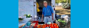 farmer Steve standing behind table at market with tomatoes