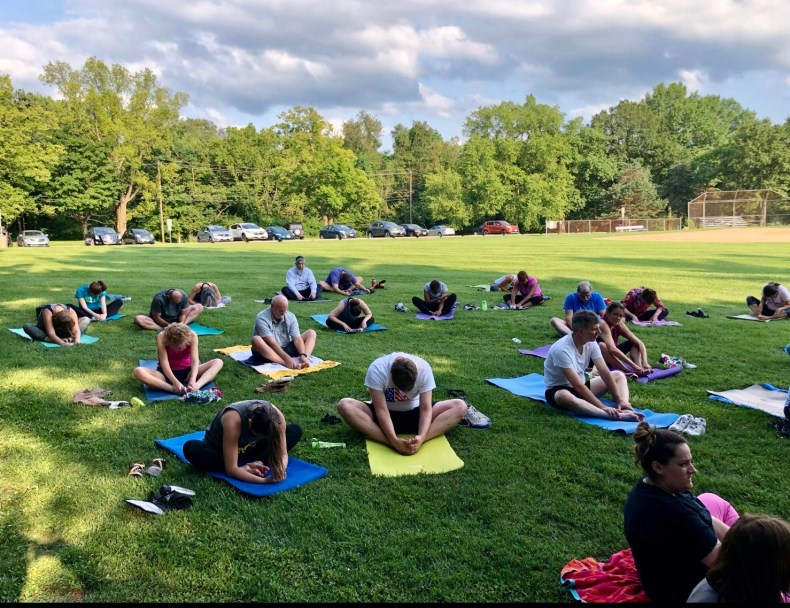 outdoors on grass, group of people sitting on yoga mats