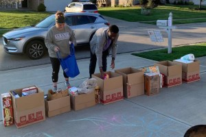 driveway with bags and boxes of items, two people dropping things off