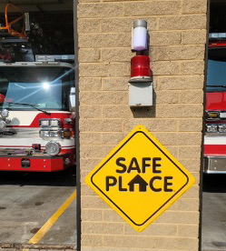 brick wall with fire trucks in background and safe place sign