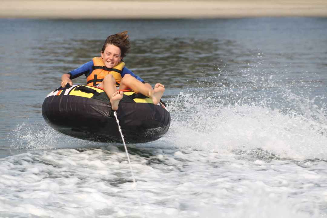 A young boy tubing on the Upper Rideau Lake close to Watercolor Westport.