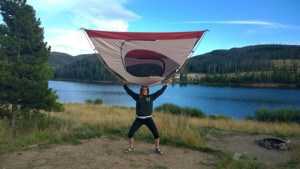 Young woman holding up a tent in front of a mountain lake in Colorado.