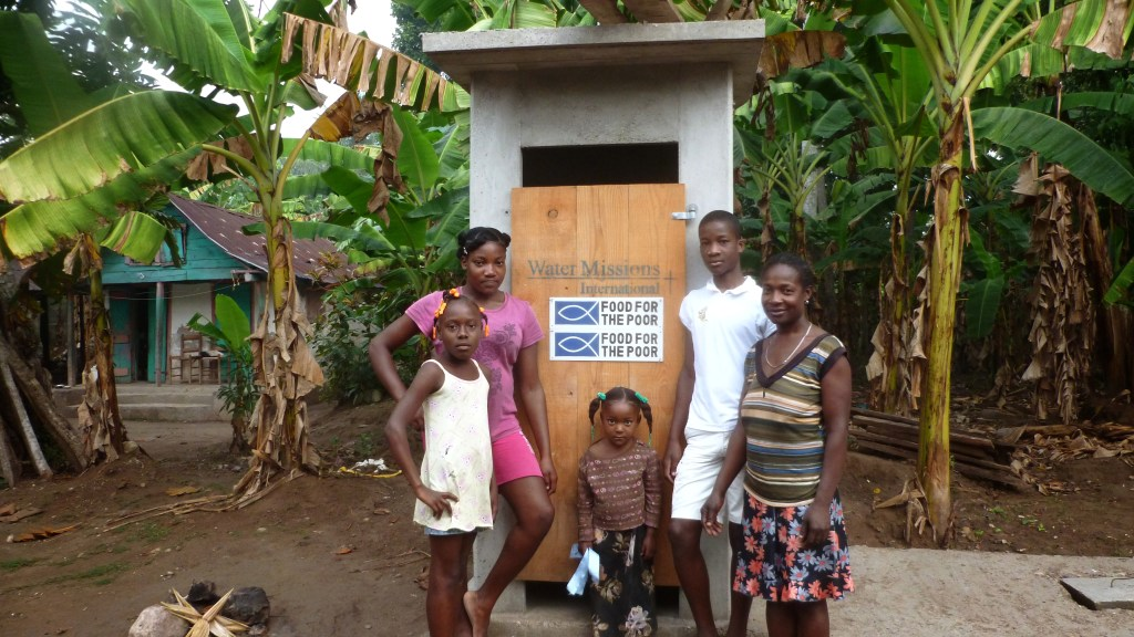 A Haitian family with a latrine