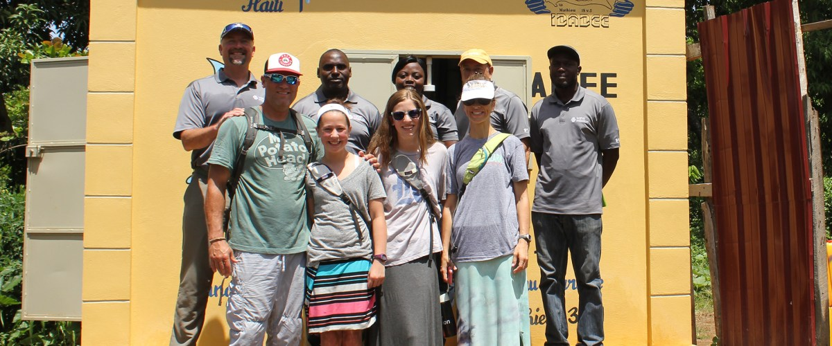The Berkman family, front, stand with Scott Linebrink and Water Mission Haiti staff by a water treatment house funded by the family.