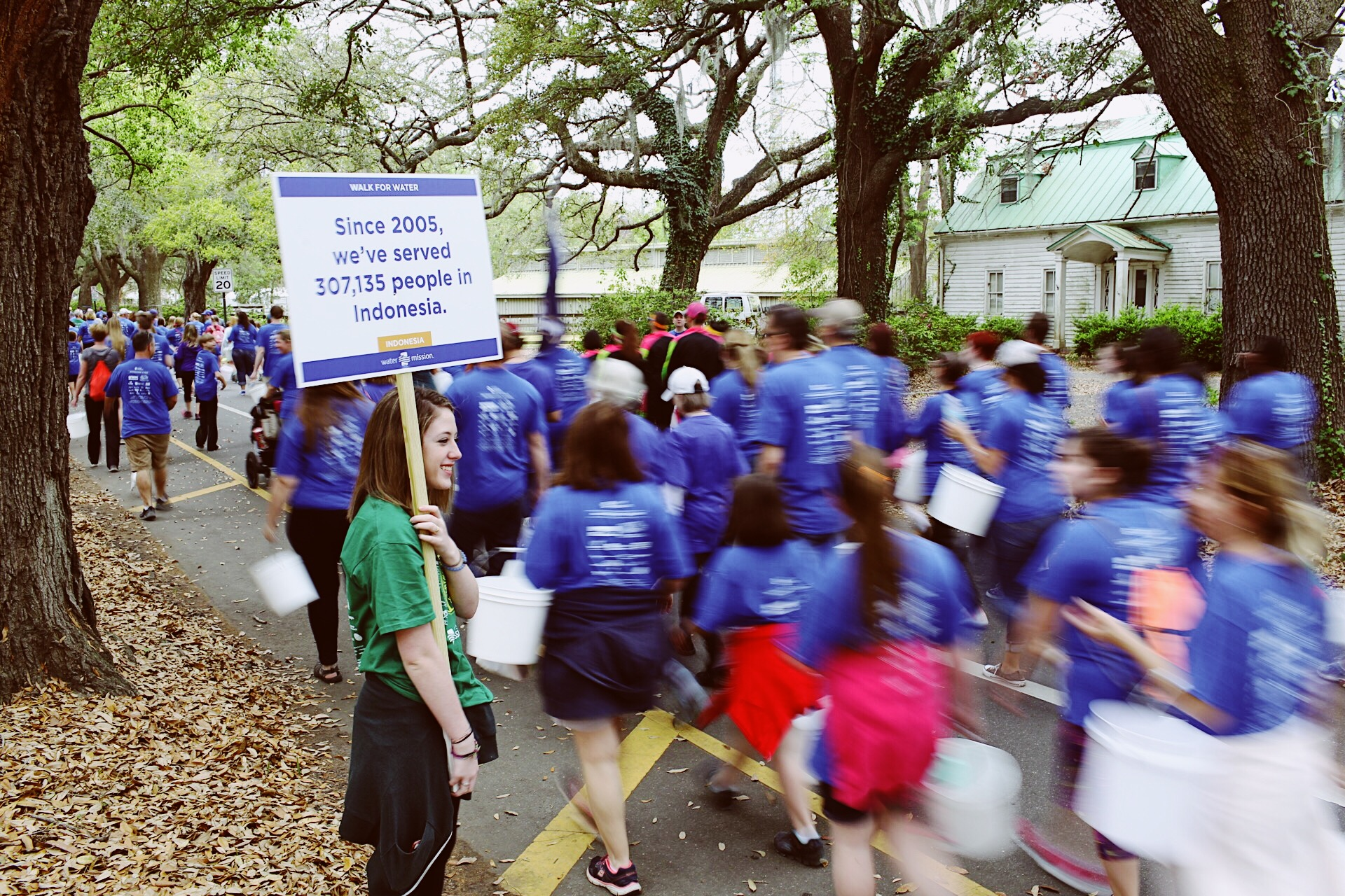 A volunteer holds a fact sign along Water Mission's Walk for Water route.