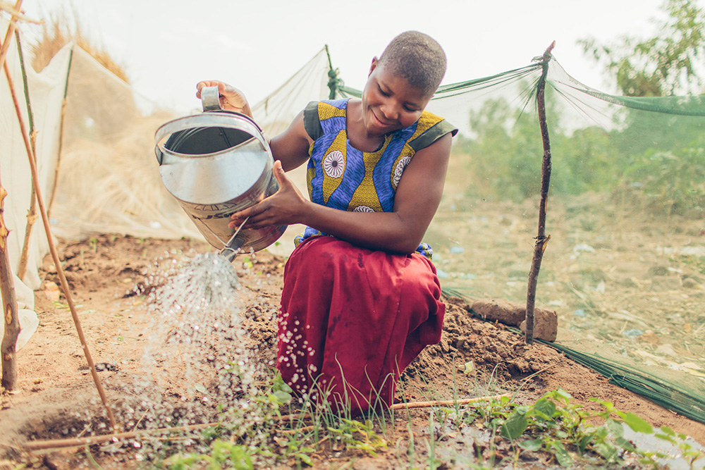 A woman waters her garden which was made possible by the safe water treatment system.A woman waters her garden which was made possible by the safe water treatment system.