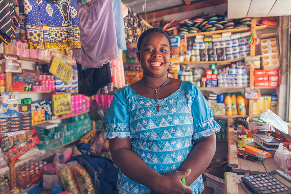 A woman smiles as she proudly stands in her shop.