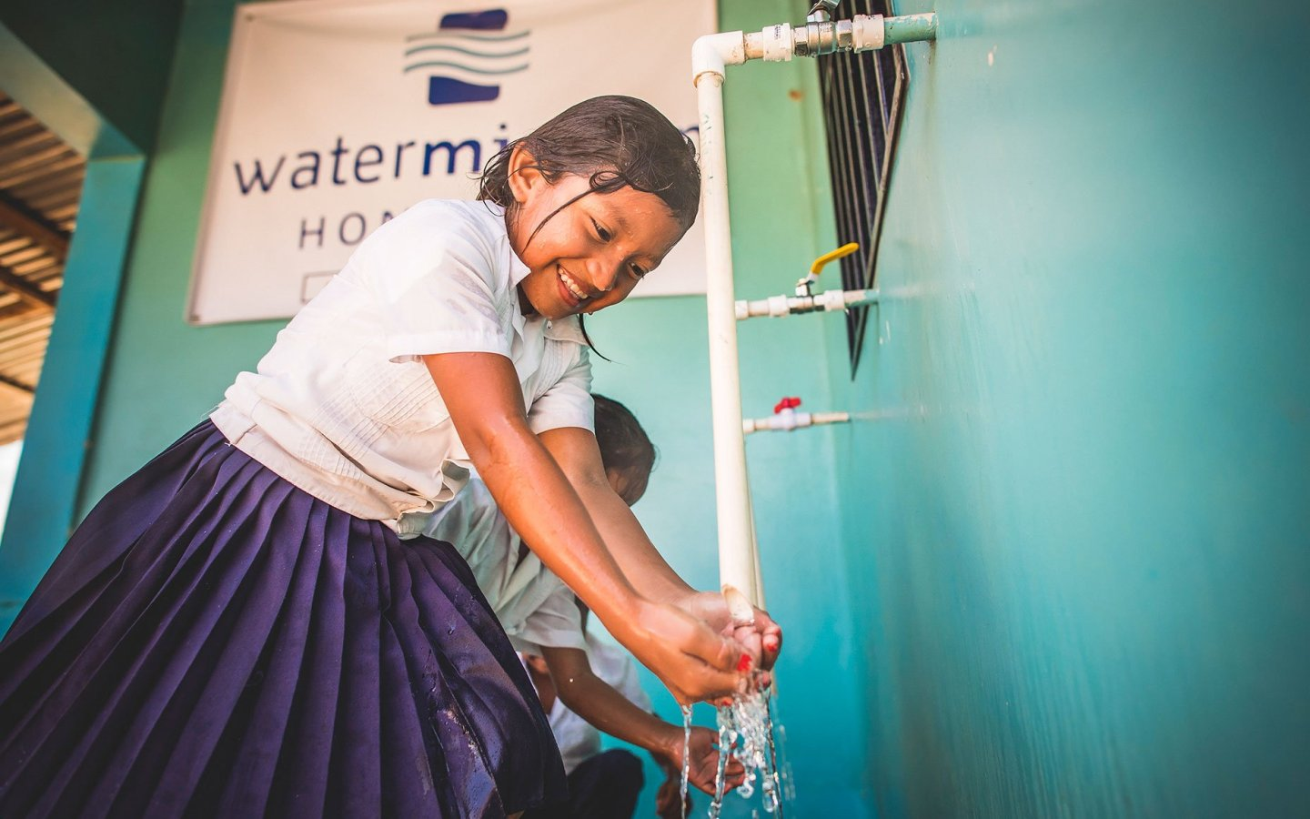 A young girl collects safe water from a Water Mission safe water treatment system in Honduras.