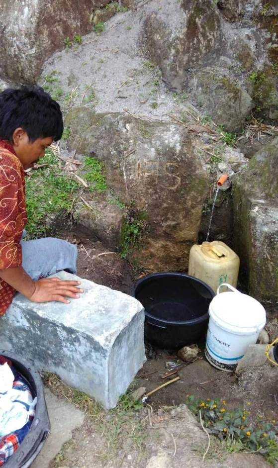 A community member gathers dirty water in Huta Ginjang, Indonesia.