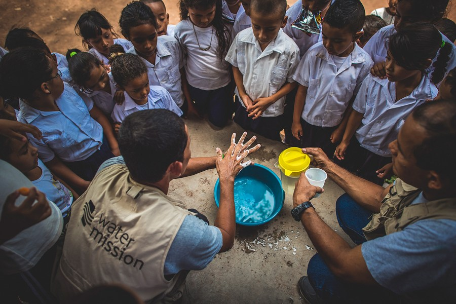 A community WASH promoter teaches students how to wash their hands.