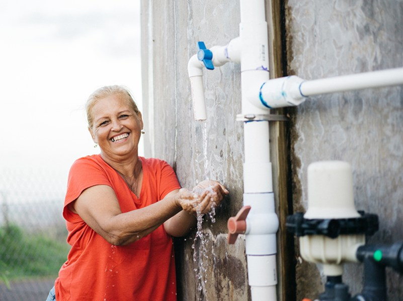 A woman smiles after safe water is restored to her community.