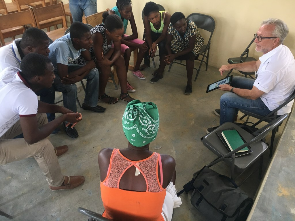Survey participants in Haiti learn the results of the survey they've taken.