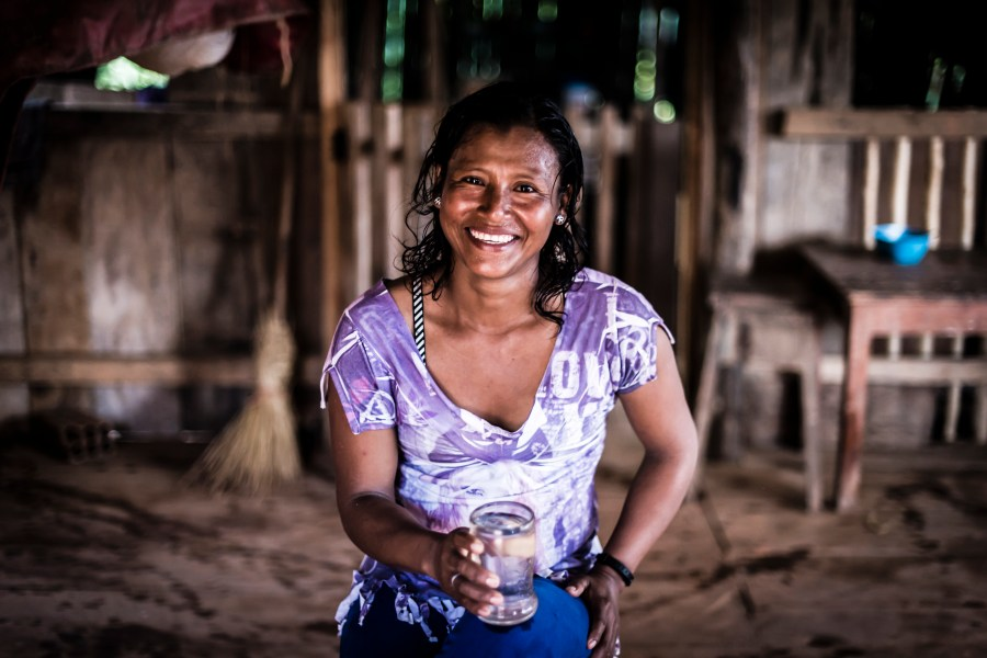 A woman in Peru smiling with a glass of clean water.