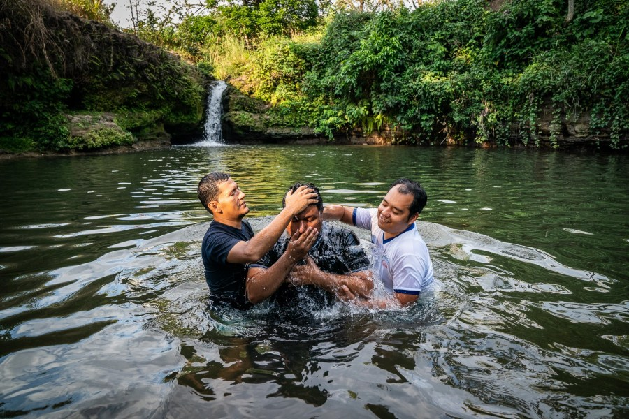 Two men help perform a water baptism for a new brother in Christ.
