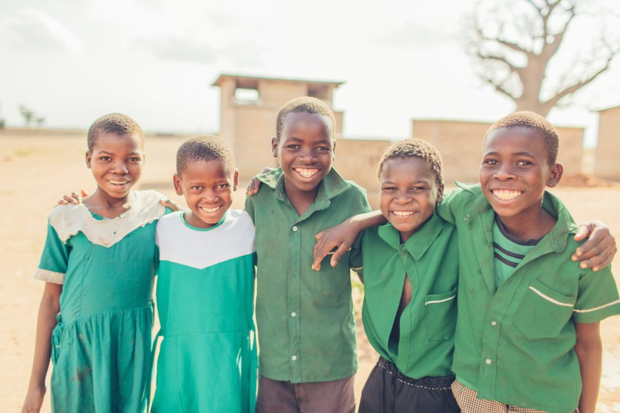 Children in Malawi smile together outside of their school.