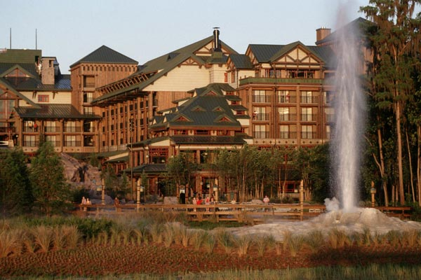 View of the back of Disney Wilderness Lodge with view of spraying geiser in background 600