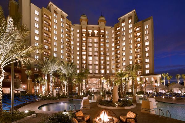 Evening View of the Wynham Grand Orlando at Bonnet Creek lit up from the Pool with Cabanas in the background 600