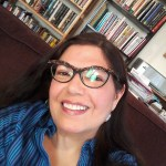 This is a head shot image of writer Mona Susan Power. Mona is wearing glasses and a blue plaid shirt. She has brown hair and she is looking directly at the camera, smiling.