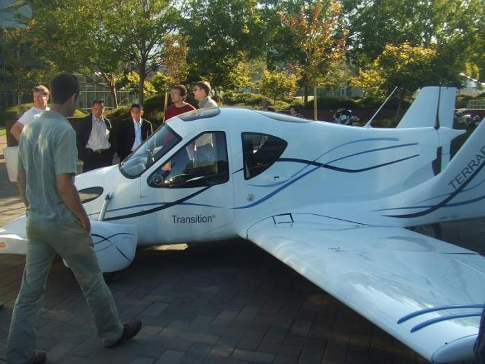 Terrafugia's flyable prototype Transition airplane, later assigned tail number N302TF, being shown during SciFoo 2008 at Google's headquarters in Mountain View, California. Just behind the airplane are two of Terrafugia's founders: Samuel Schweighart (L, red shirt), VP of Engineering; and Carl Dietrich (R, beige shirt), CEO/CTO.