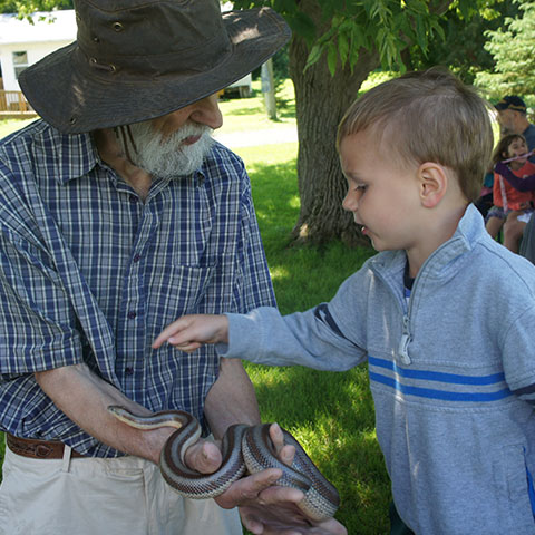 Man showing little boy a snake