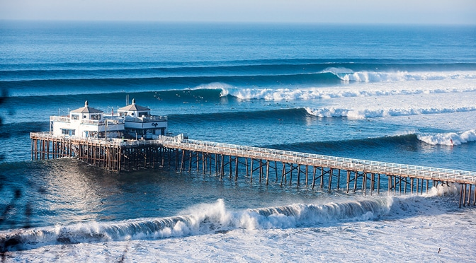 the Malibu pier surrounded by a bright blue ocean stacked with big waves breaking into foamy white wash