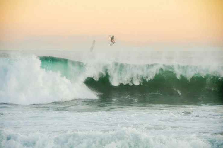 a surfer and his board flying above the wedge: a large, green, barreling wave at newport beach
