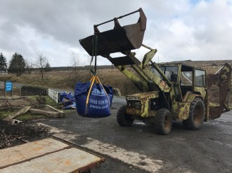 The Hymac 370 digger is used to move the dumpy bags of fine stone, and load the type B trolley