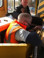 Baz squeezes himself into the Permaquip's engine bay to try and tension the alternator belt