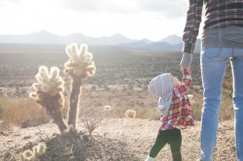 Kid holding fathers hand in desert