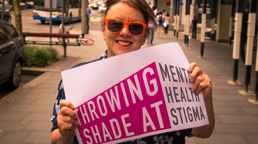 Liz showing off the new slogan launched by WayAhead, Being and Mental Health Carers NSW at Fair Day 2018