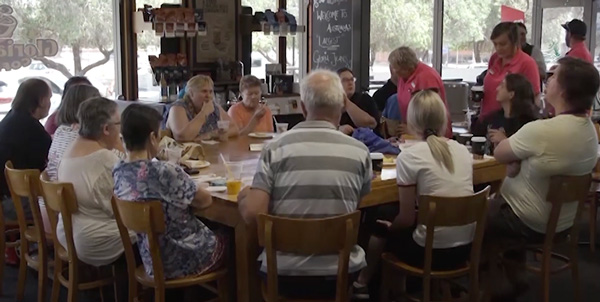 Participants of the connections program sitting around a large table at a cafe