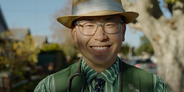 Dr Ho wearing a striking green tailored suit that he made himself, he is smiling