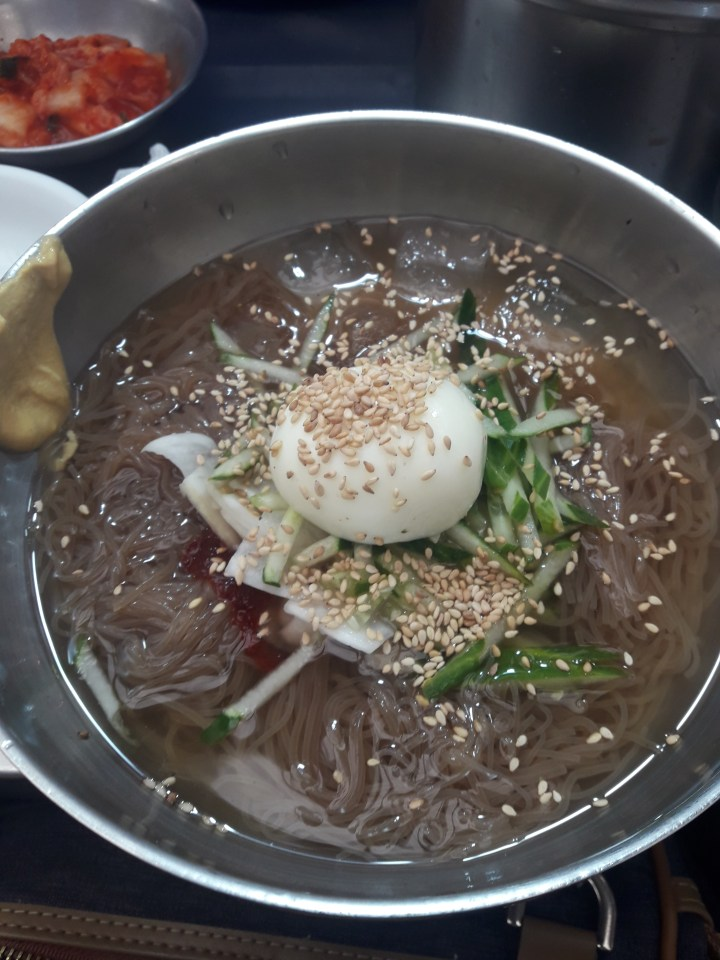 a metal bowl with thin brown noodles, thin sliced cucumber sticks, thin sliced radish, a boiled egg and a lot of seasame seeds in a clear brooth with a little bit of red gochujang peeking through and some brown spicy mustard on the side of the bowl. In the background is a metal bowl of kimchi.