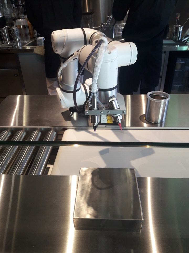 A white robotic arm with a couple of different colored pens waiting for a cake to decorate above a conveyor belt.