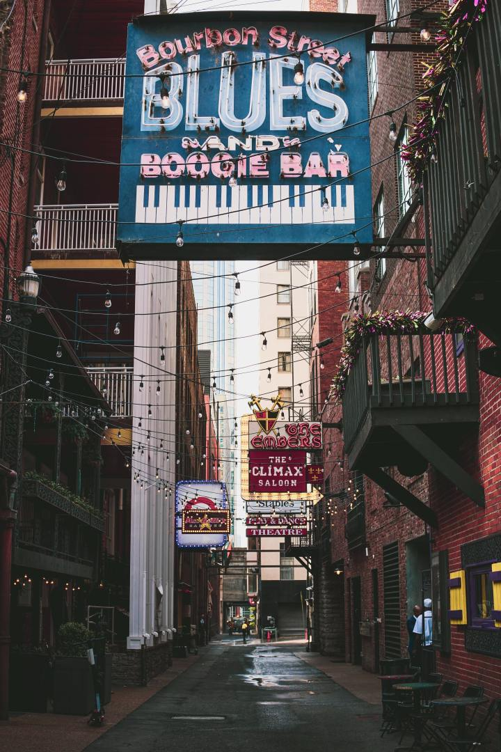"Viewer is in the middle of a one way road that has an alley feel due to the narrowness. It is day time. Between brick buildings and balconies covered in flowers or tinsel are large neon signs unlit. The nearest is a large blue one with a piano painted on the bottom of it. It states ""Bourbon Street Blues and Boogie Bar"" lights are unlit and strewn between buildings and several other neon unlit signs are further in the background including ""the embers"" ""The climax saloon"" and ""theater"" Taken according to the photographer in printer's alley nashville"