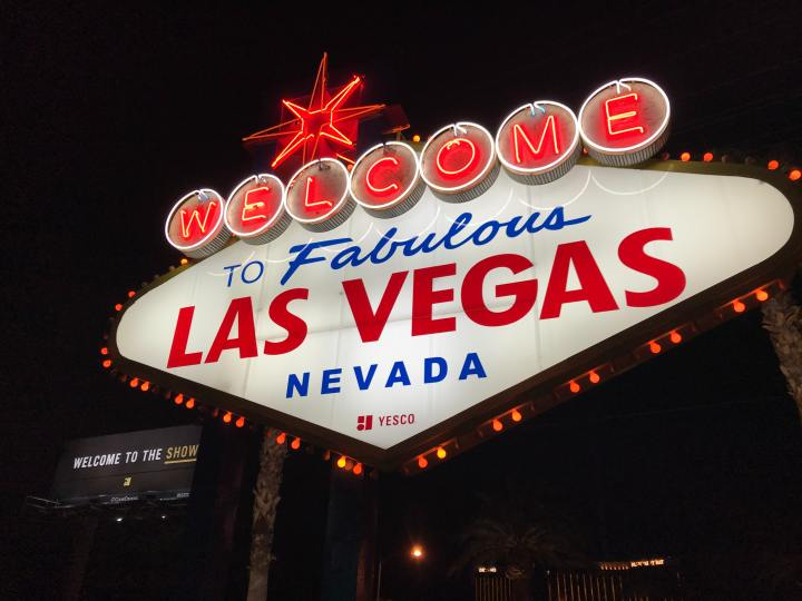 "The neon sign stating Welcome to Fabulous Las Vegas Nevada in small print below it says Vesco and in the background is a billboard saying Welcome to the Show, ""show"" is yellow and underlined."