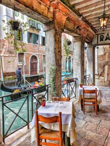 Small tables on stone with two chairs at each table along the water as a gondolier passes on the blue waters between buildings in Italy.