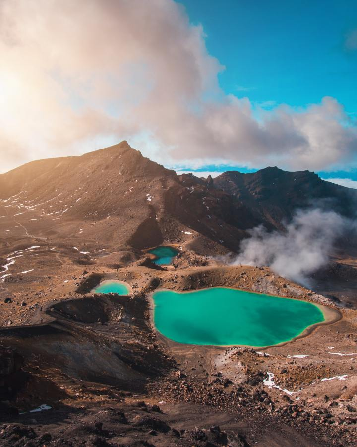 A view from above at some mountains and in-between the mountains are three bodies of water that are green colored. One large one and two small ones. Some clouds, possibly steam is coming off from behind a small hill next to the largest pond. Taken according to the photographer at Tongariro National Park, New Zealand